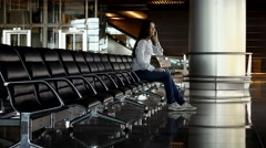 Woman sit alone at empty row of seats, answer on phone, terminal lounge Stock Footage