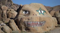 A young man trail running by a boulder with a happy smiling face painted on it i Stock Footage