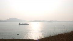 Cargo ship on shiny harbour waters. Island in fog on background Stock Footage