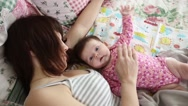 A child plays with his mother lying Stock Footage
