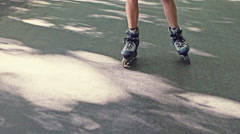 Feet of a woman roller skating on tarmac Stock Footage