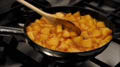Apples cut into pieces grilling in a pan with sugar Stock Footage