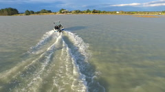 Aerial shot of young man wake boarding behind a motorboat in a lake. Stock Footage