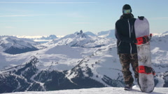 A young man snowboarder standing with his snowboard on a snow covered mountain. Stock Footage