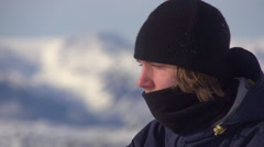 Portrait of a young man snowboarder on a scenic snow covered mountain top. Stock Footage