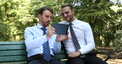 Business Men Presentation Work on Tablet Sitting a Park Bench near Green Trees Stock Footage