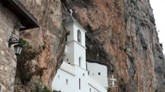People take pictures with one of two churches in rock. Upper Ostrog Monastery Stock Footage
