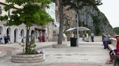 Benches for people resting are on square near church built in cave. Upper Ostrog Stock Footage