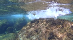 Waves splashing over the rocks under water, slow motion Stock Footage