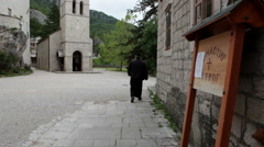Monk walk on the courtyard of lower monastery of Ostrog. Montenegro Stock Footage