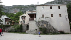 Visitors walk in courtyard of lower monastery of Ostrog. Montenegro Stock Footage