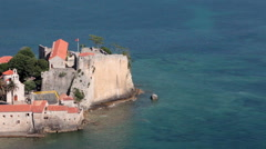 Aerial view at well preserved medieval walled town on Adriatic peninsula. Budva Stock Footage