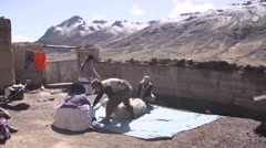 Local people shearing wool from llama Stock Footage