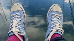 Blue sneakers and pink socks over water background. Stock Footage