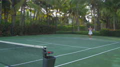 A young woman playing tennis with her boyfriend while on vacation. Stock Footage