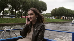 Young woman talks on the phone on a river tour, sightseeing, happily smiling Stock Footage