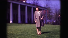 1946: woman stands in front of an impressive towering building while people walk Stock Footage