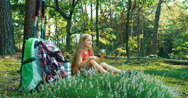 Hiker girl child 8-9 years relaxing and drinking tea in the forest and smiling Stock Footage