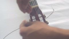 Restringing Your Classical Guitar (turning) side view Stock Footage