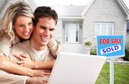Couple with laptop near new house. Stock Photos