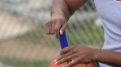 A young man basketball player inflating basketball. Stock Footage