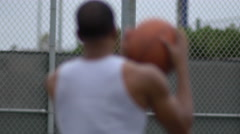 A young man shooting hoops on an outdoor basketball court. Stock Footage