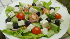 Oil pouring into bowl of greek salad Stock Footage