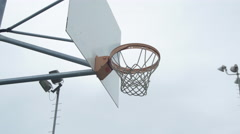 A young man basketball player dunking on an outdoor basketball court. Stock Footage