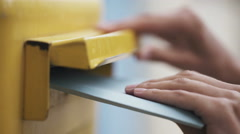 Woman is sending a blue letter into a yellow letterbox. 4K Stock Footage