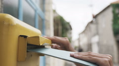 Woman is sending a blue letter into a yellow letterbox. Slow motion 120 fps Stock Footage