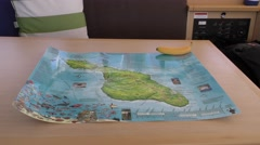 Map of island on sail boat's cabin table with a banana Stock Footage