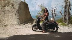Beautiful woman sitting on black vespa scooter Stock Footage