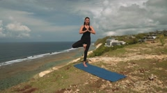 Woman in tree yoga pose on edge of cliff on Bali shore Stock Footage