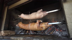 Pig is roasting on a spit Stock Footage