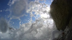 Sideview, waves splashing over the wavebreaker against the sun, slow motion Stock Footage