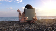 Beautiful girl looking at tablet in the beach at sunset with sunshine Stock Footage