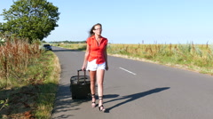 4K. Adult sexy woman in red blouse  with  suitcase on  road. Steady shot Stock Footage