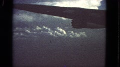 1963: wing of an airplane view from passenger window seat flying over clouds Stock Footage