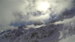 Sun shinning on snow covered mountain peaks. Stock Footage