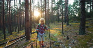 Hiker girl 8-9 years child goes at camera in the forest Stock Footage