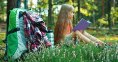 Hiker girl child 8-9 years reading book in the forest and laughing Stock Footage