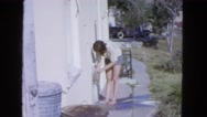 1963: brunette woman turning on faucet at side of house CALIFORNIA Stock Footage