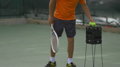 Male tennis player gathering tennis balls with racket. Stock Footage