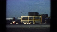 1963: view of large airport with many vehicles and huge airliners ready to load Stock Footage