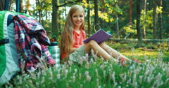 Hiker girl child 8-9 years reading book in the forest and looking at camera Stock Footage