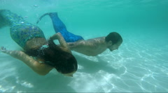 Mermaid couple swimming underwater from tropical beach Stock Footage