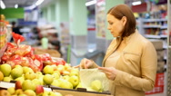 Woman buys apples at the supermarket Stock Footage