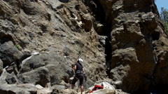 A woman belaying a man while rock climbing. Stock Footage