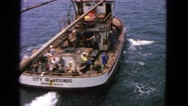 1963: commercial fishing boat heading out of port busy with men working Stock Footage