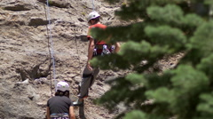 A young man repelling down a mountain while rock climbing. Stock Footage